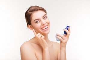 Beauty portrait of a smiling woman holding moisturizing facial cream isolated on a white background