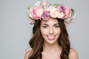 Beauty portrait of a smiling woman with wreath from flowers on head looking at camera over gray background