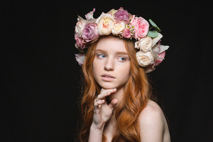 Beauty portrait of a young redhead woman with wreath from flowers on head looking away over black background
