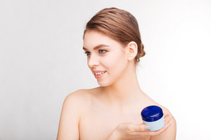 Beauty portrait of a young woman holding moisturizing facial cream isolated on a white background