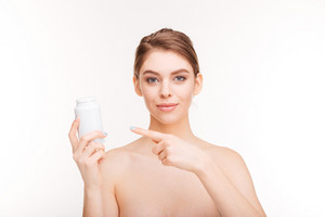 Beauty portrait of a young woman pointing finger on bottle with pills isolated on a white background