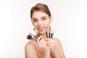 Beauty portrait of attractive smiling young woman holding makeup brushes