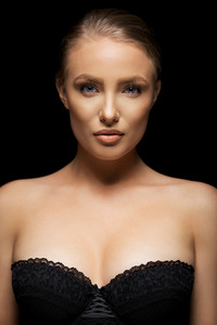 Beauty portrait of stunning young female model wearing black underwear. Blue eyes and blond hair.