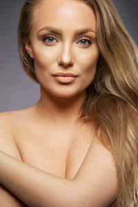 Beauty portrait of young caucasian girl on grey background. Close up of sexy female fashion model topless.