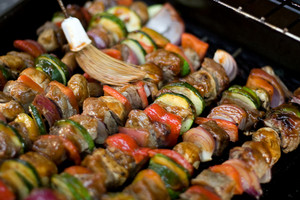 Beef shish kebabs on skewers, cooking on the grill.  Shallow depth of field.