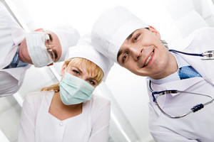 Below view of happy doctors with nurse between them looking at camera