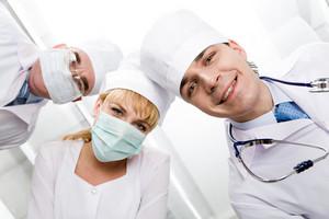 Below view of happy doctors with nurse between them looking at camera