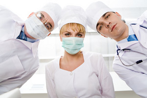 Below view of three therapeutists in masks looking at camera
