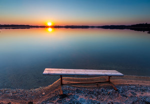 Bench on lake shore at sunset. Beautiful landscape photographed in Poland.