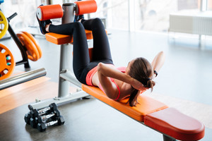 Beutiful strong young woman athlete doing abdominal crunches on bench in gym
