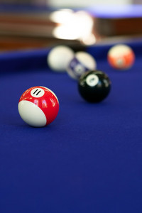 Billiard balls on a purple fabric pool table. Shallow depth of field with sharpest focus on the 11 ball.