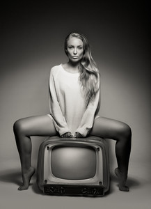 Black and white portrait of young woman sitting on old television over grey background.