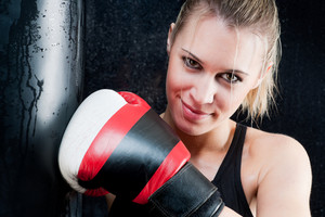 Blond boxing training woman with gloves in gym