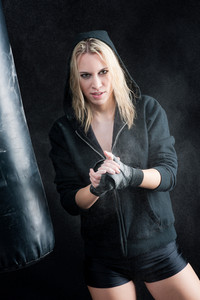 Blond boxing woman prepare for training with punching bag