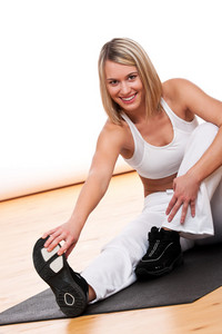 Blond woman in white outfit exercising on mat