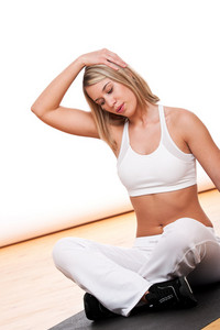 Blond woman stretching on black mat