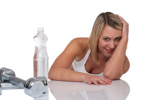 Blond woman with bottle of water and weights on white background