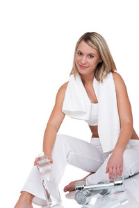 Blond woman with weights and bottle of water on white background