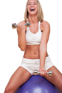 Blond woman with weights sitting on purple ball