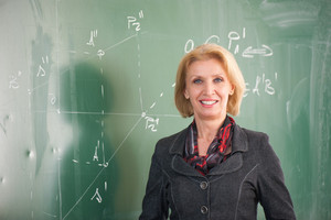 Blonde caucasian female teacher posing on a blackboard