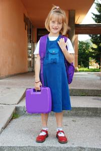 Blonde girl in front of the school standing