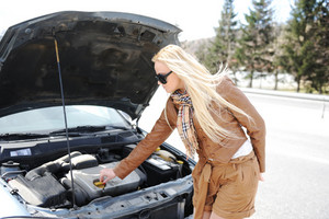 Blonde girl trying to fix her broken car