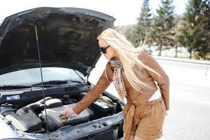 Blonde girl trying to fix her broken car