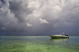 Boat moored in a tropical harbor under a stormy sky