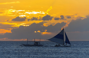 Boat towing a sailboat in the ocean during a dramatic sunset