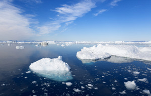 Boat traveling by sunlit ice floes