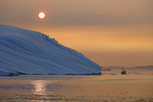 Boat traveling past an iceberg at sunset