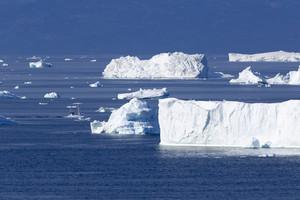 Boat traveling past sunlit icebergs