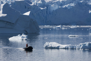 Boater traveling past sunlit icebergs