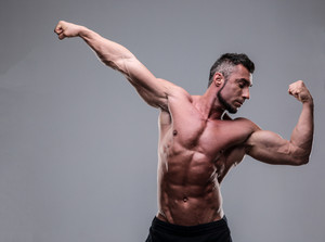 Bodybuilder posing over gray background