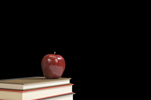 Books and Apples Against Empty Chalkboard