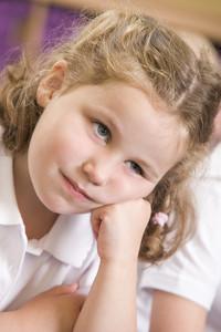 Bored schoolgirl sitting in primary class