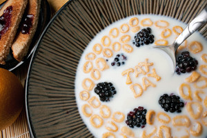 Bowl of cereal with blackberries and letter shaped pieces spelling the words TAX DAY floating in a milk.