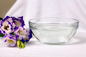 Bowl of water on white towl with eustoma flower