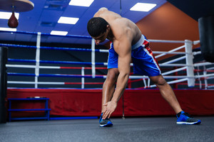 Boxer doing warm up exercises near boxing ring