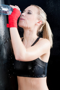 Boxing training woman pour water on face hold punching bag