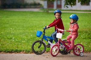Boy And Girl In Nature With Bicycle Have Fun