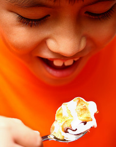 Boy Eating A Delicious Creamy Puff