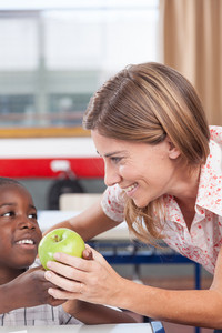 Boy giving to his teacher a apple