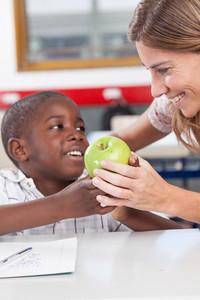 Boy giving to his teacher a apple