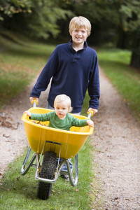 Boy giving toddler ride in wheelbarrow along path