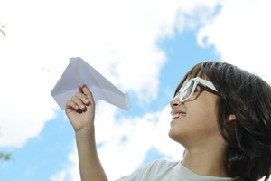 Boy holding a paper airplane dreaming about flying and traveling