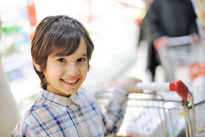 Boy holding cart in shopping mall