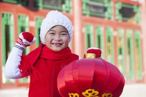 Boy holding lantern dressed in holiday attire