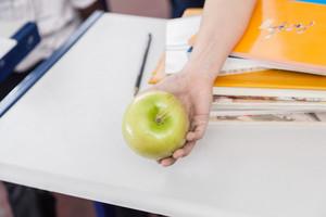 Boy offering a green apple