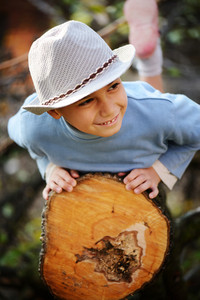 Boy portrait on timber tree outdoor in nature
